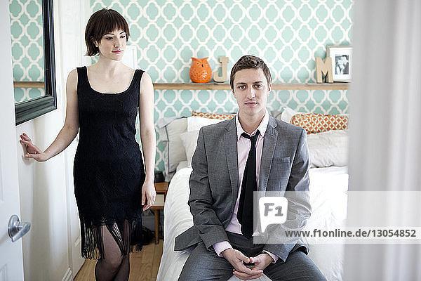 Sensuous woman looking at man wearing suit in bedroom