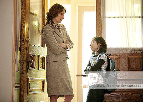 Mother and daughter looking at each other while standing at door