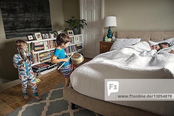 Kinder spielen mit Utensilien  während die Eltern zu Hause im Bett liegen