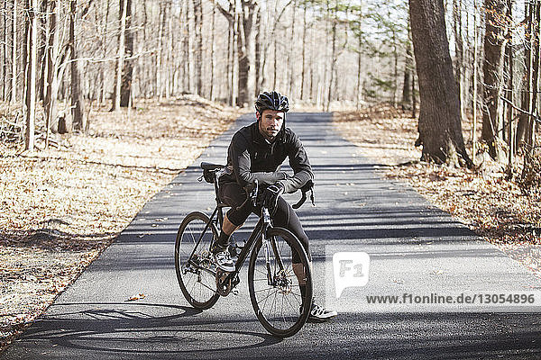 Portrait of cyclist with bicycle standing on road at forest