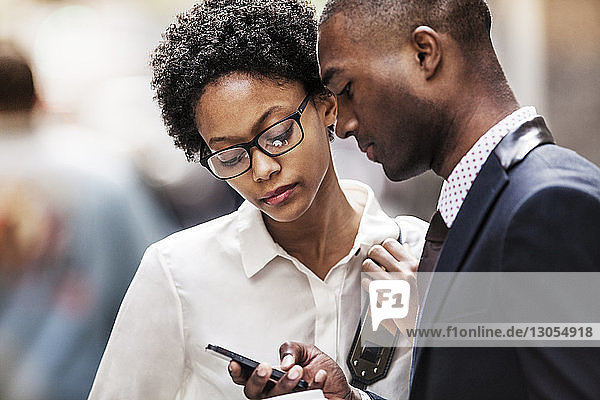 Businessman and businesswoman looking at smart phone while standing at city street