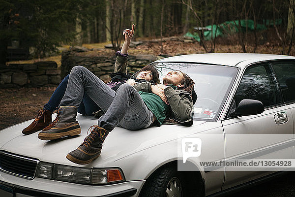 Couple lying on car in forest