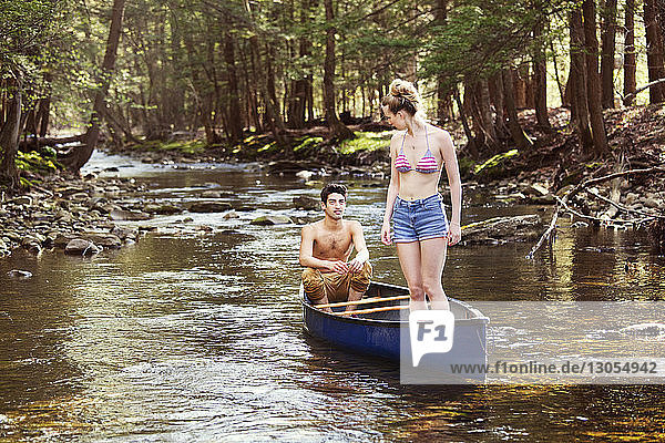 Man looking at woman standing on rowboat in river