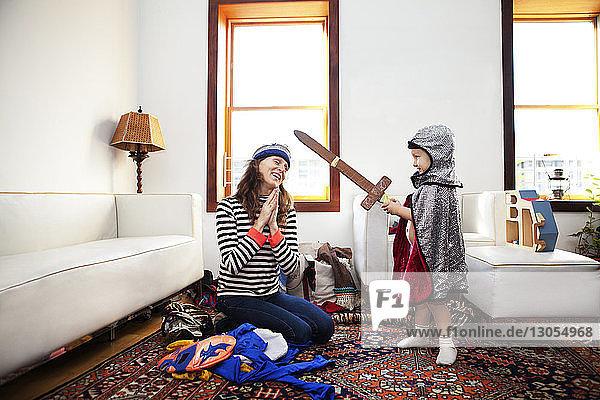Junge im Ritterkostüm spielt zu Hause mit der Mutter