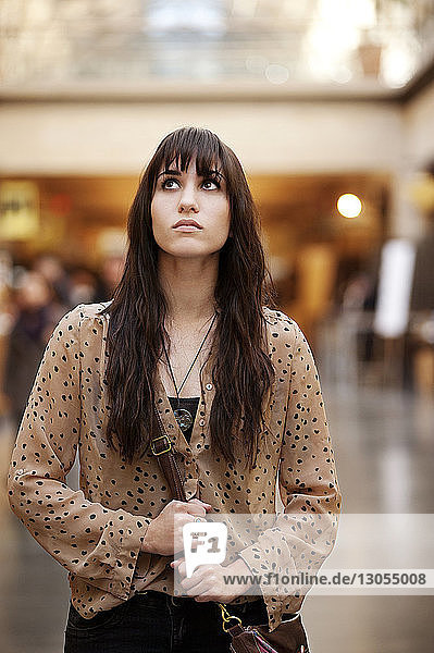 Woman looking up while standing in shopping mall