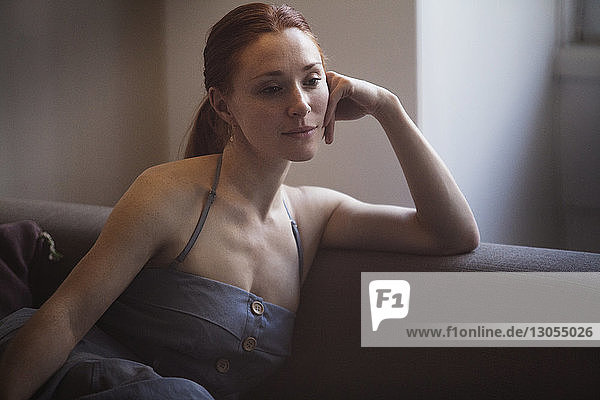 Thoughtful woman sitting on sofa at home