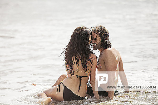 Romantic couple sitting on shore at beach during summer vacation