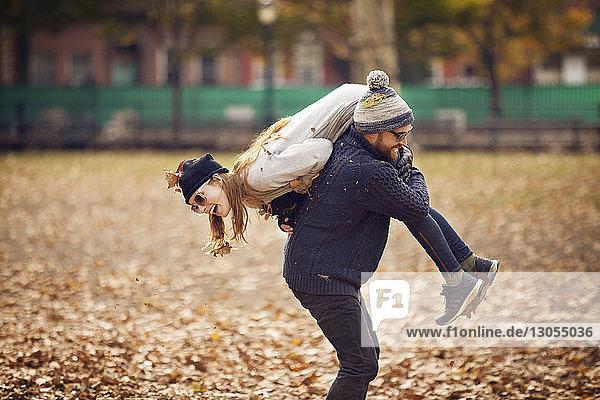 Mann trägt Frau auf der Schulter  während er im Park steht