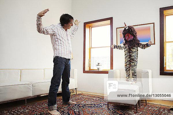 Junge in Tierkostüm steht mit Vater zu Hause