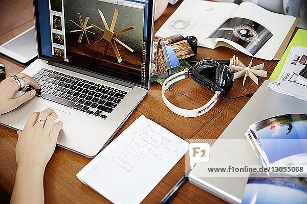 Ausgeschnittenes Bild einer Geschäftsfrau  die am Schreibtisch am Laptop arbeitet