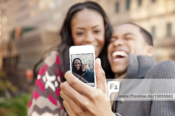 Cheerful young couple clicking selfie with smart phone
