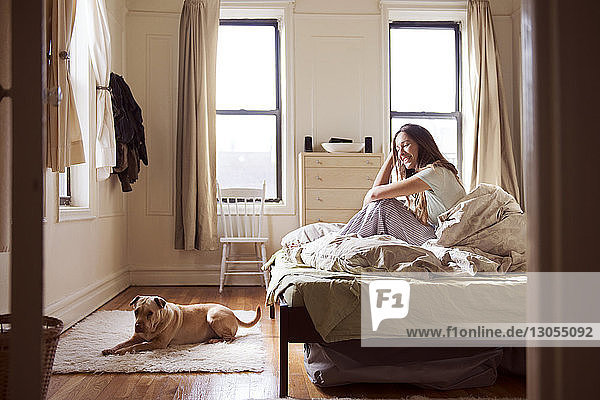 Happy woman sitting on bed and looking at dog