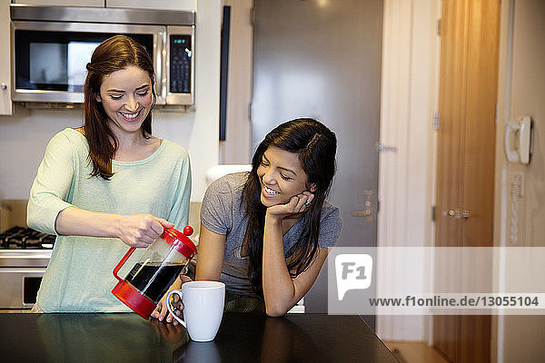Smiling woman serving coffee to female friend at home