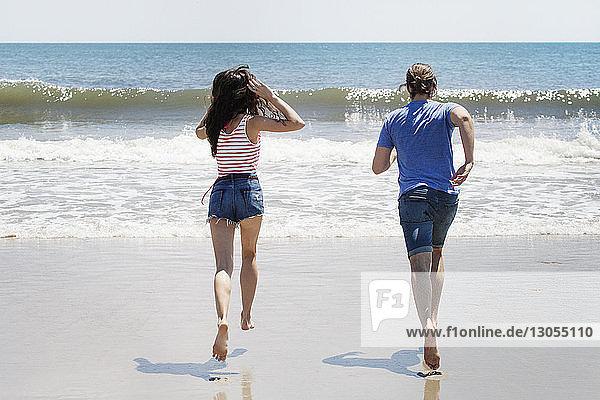 Rückansicht eines am Strand an Land laufenden Paares
