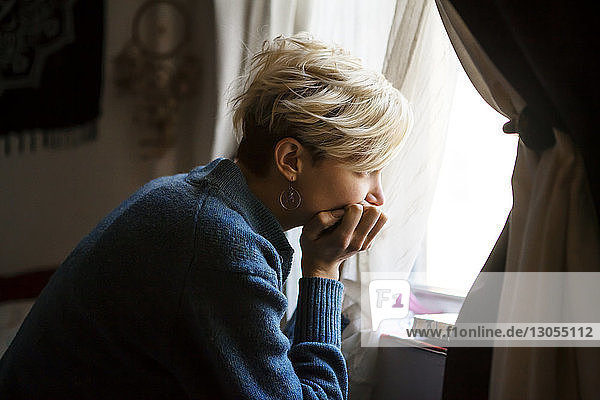 Woman with hand on chin looking away though window at home