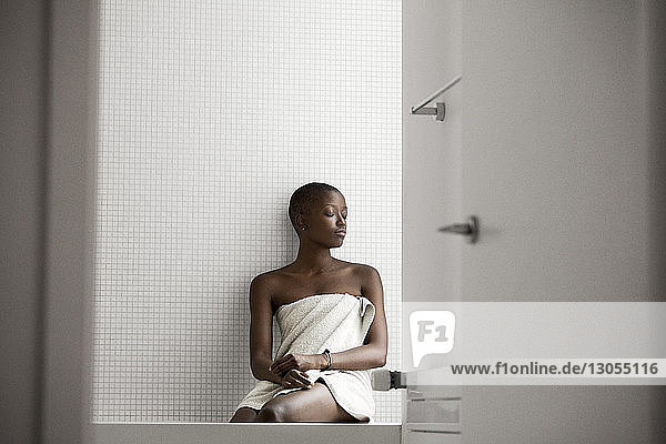 Woman with eyes closed sitting in bathroom