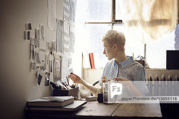 Woman sticking photographs on wall while sitting by table at home