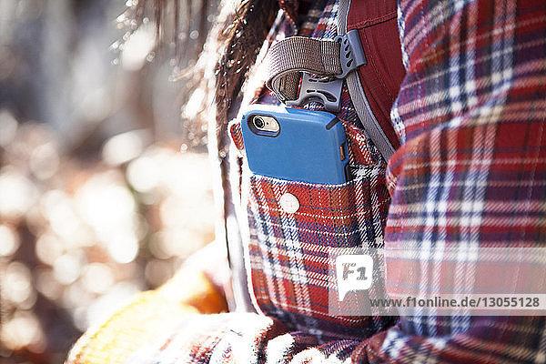 Mitschnitt einer Frau mit Smartphone in der Tasche