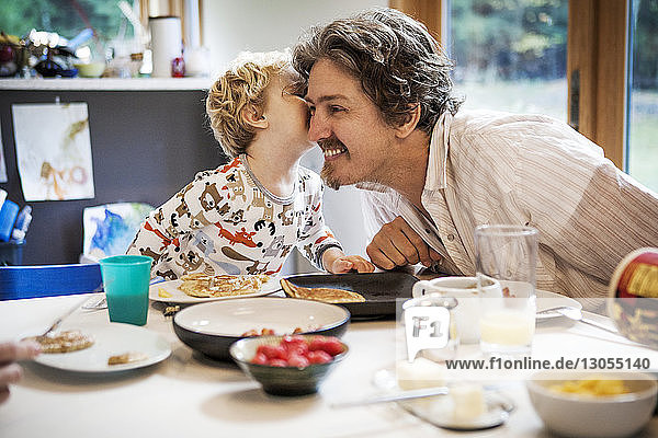 Boy kissing father at dinning table in home