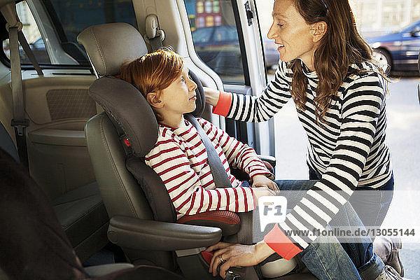 Mutter spricht mit Sohn  während sie im Auto angeschnallt ist