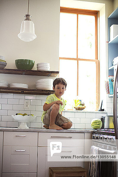 Portrait of boy sitting on kitchen counter