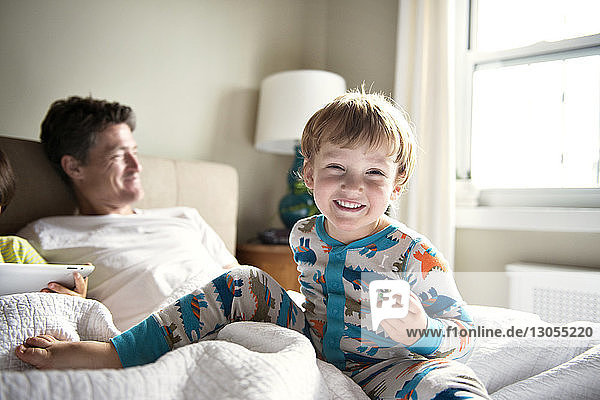 Happy boy enjoying with father while brother using tablet computer on bed at home