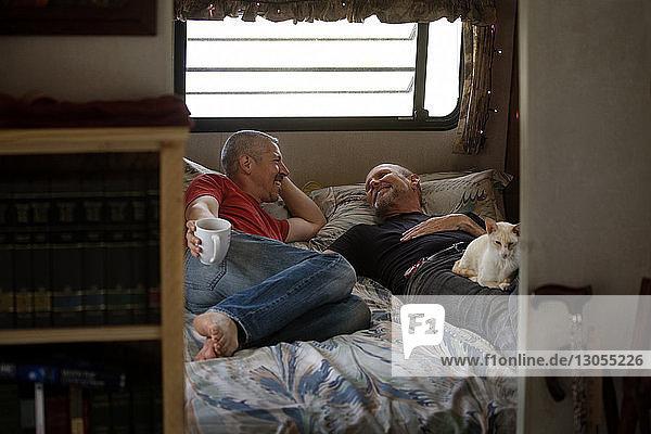 Glückliches schwules Paar schläft im Bett im Wohnmobil