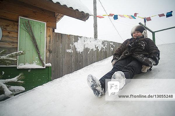 Glückliche Schlittenfahrerin auf schneebedecktem Hügel