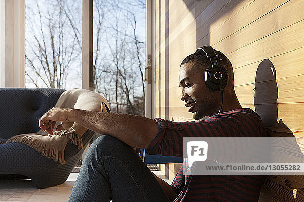 Happy man listening music on headphone while sitting at home