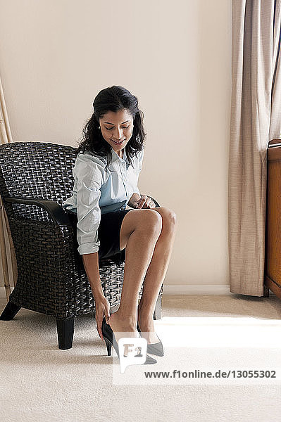 Happy businesswoman wearing shoes while sitting on sofa at home
