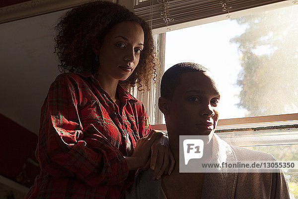 Portrait of couple standing by window at home