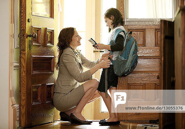 Mother adjusting daughter's bag while crouching at door