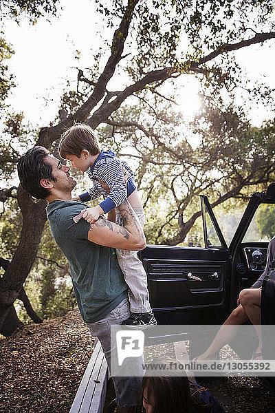 Mann hebt Jungen hoch  während er mit Familie im Wald steht