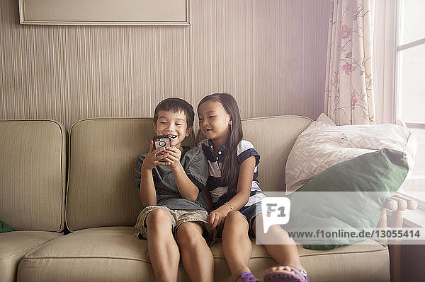 Smiling siblings using phone while relaxing on sofa