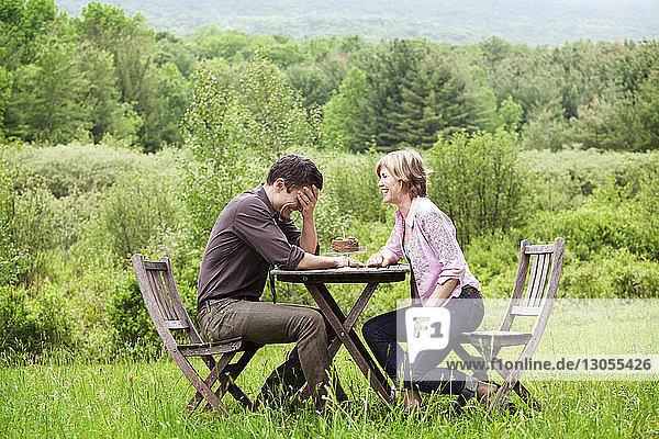 Seitenansicht eines auf einem Stuhl sitzenden Paares im Feld