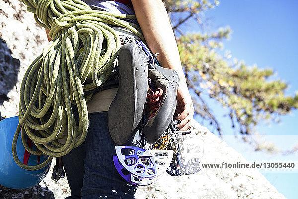 Mitschnitt einer Frau mit Kletterausrüstung am Fels stehend