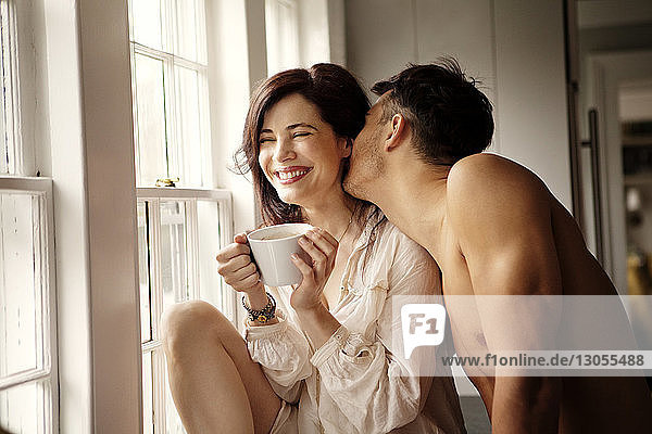 Fröhliches Paar genießt es  zu Hause am Fenster zu sitzen