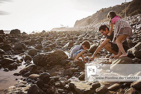 Vater mit Kindern genießt am Strand bei Sonnenuntergang