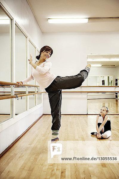 Mädchen sieht Lehrerin beim Tanzen an  während sie auf dem Boden sitzt
