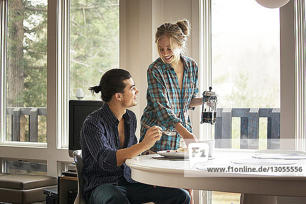Couple talking while sitting by breakfast table at home
