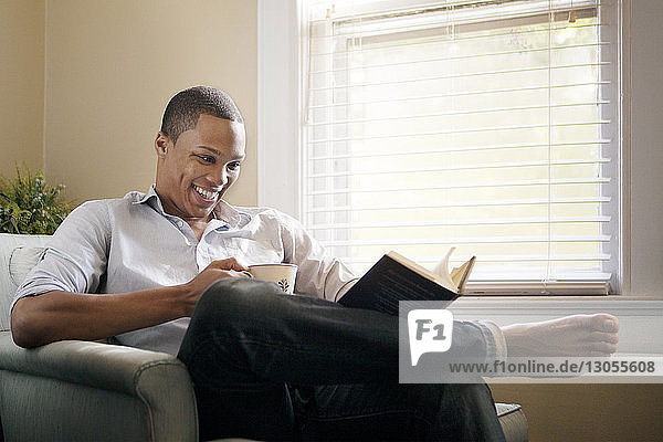 Happy man reading book while sitting on arm chair at home