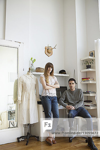 Portrait of male and female fashion designer in studio