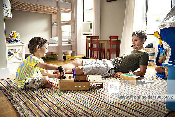 Happy father looking at boy playing with toy at home