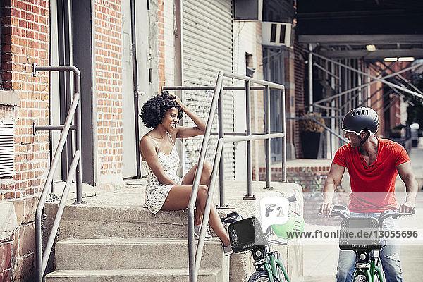 Frau sitzt auf Stufen und schaut auf Mann mit Fahrrad