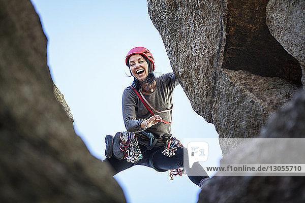 Niedrigwinkelansicht einer glücklichen Frau beim Felsklettern