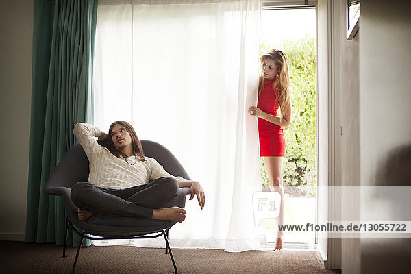 Woman with tip-toe looking at man sitting on chair at home