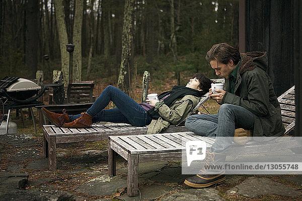 Ein Paar trinkt Kaffee  während es sich auf einem Liegestuhl auf dem Campingplatz entspannt