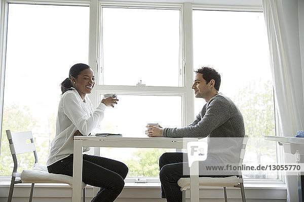Male and female colleagues having coffee at table in office