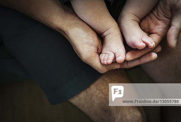 High angle view of father holding baby boy's feet