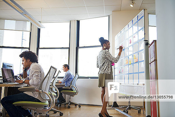 Businesswoman writing on whiteboard while colleagues working in creative office